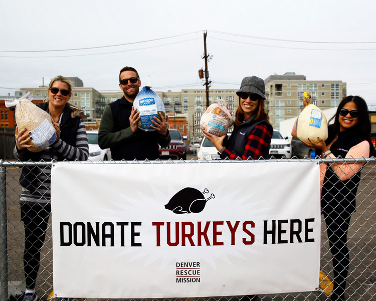 Turkey donors holding turkeys next to a Donate Turkeys Here sign.